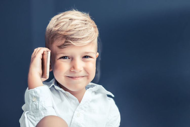 Portrait of cute boy against blue background