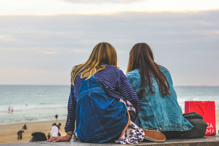 Rear View Of Friends Sitting At Beach Against Sky