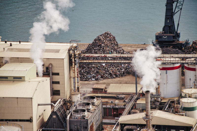 High angle view of smoke emitting from factory at recycling center at commercial dock, barcelona