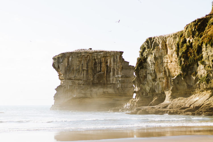 Scenic view of rock formation and sea against clear sky