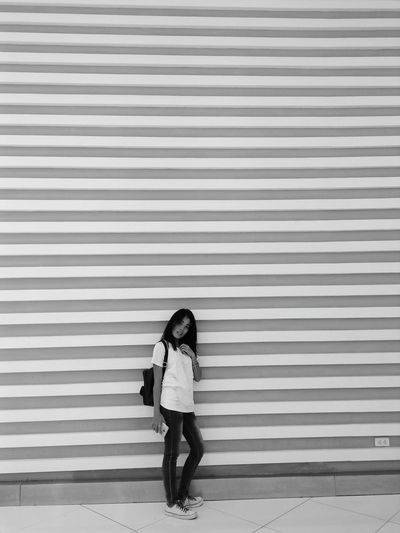 Portrait Of Young Woman Standing Against Patterned Wall