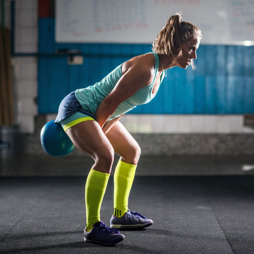 Side View Of Mid Adult Woman Holding Kettlebell While Standing In Gym