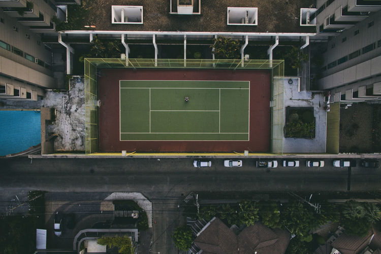 Empty roof tennis court between building drone view from above Drone  View From Above Alone Empty Lonely Tennis Court Sport High Angle View High Above Skyscraper Building Urban City City Life Urban Living Embrace Urban Life Square Symetry Tennis Court View From Above Looking From Above Looking Down From Above Looking Below Looking Down Below Flying High
