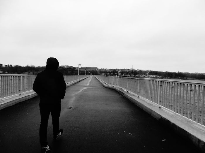 Rear view of woman standing on bridge against clear sky