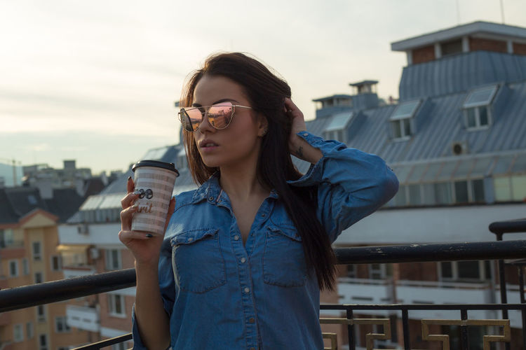Young woman holding disposable cup while standing on building terrace