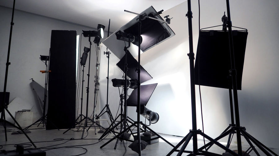 Lighting setup in studio for commercial works such as photo movie or video film production which use many LED light more than 1000 watts with big softbox snoot reflector umbrella and tripods. Arts Culture And Entertainment Behind The Scenes Camera - Photographic Equipment Creativity Digital Camera Electric Lamp Equipment Film Industry Film Studio Filming Indoors  Lighting Equipment Man Made Man Made Object Photo Shoot Photographic Equipment Photography Themes Preparation  Studio Studio Shot Studio; Photo; Equipment; Photography; Background; Professional; Photographer; Light; Camera; Empty; White; Creative; Modern; Lamp; Flash; Black; Fashion; Shot; Halogen; Photograph; Photographic; Technology; Nobody; Spotlight; Soft; Illuminated; Electrica Technology Television Studio Tripod