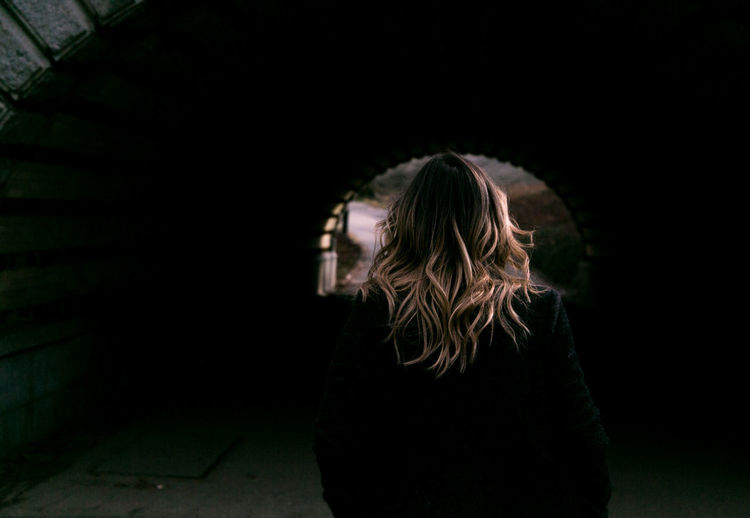 Rear view of woman with blond hair walking towards tunnel