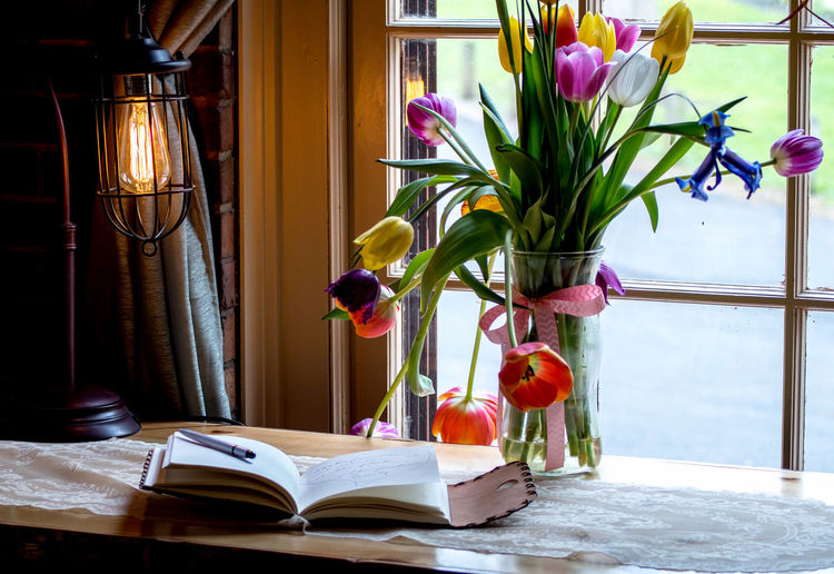 Still life with a vase of tulips, and a journal, lit with natural light and an antique lamp