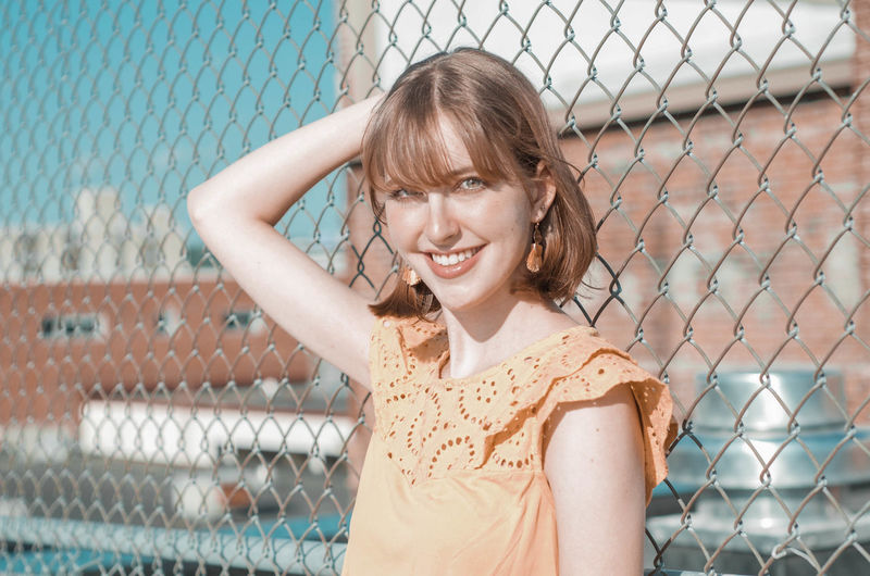 Portrait of smiling woman standing by chainlink fence