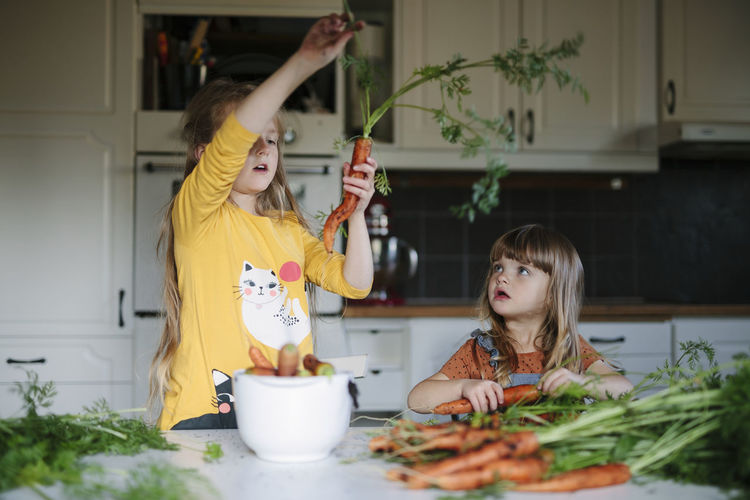 Cute girl and vegetables on table at home