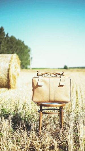Briefcase On Chair At Field Against Sky During Sunny Day