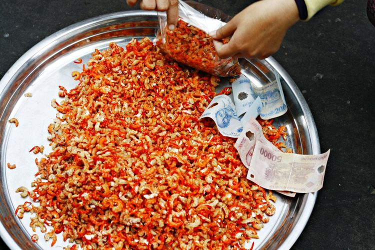 High angle view of hands packing prawns