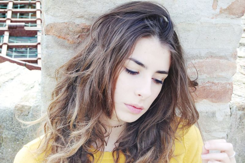 Close-Up Of Young Woman Looking Away While Standing Against Wall