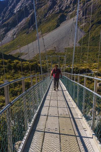 Rear view of men walking on footbridge