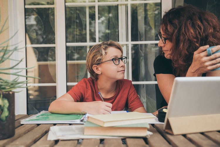 Mother teaching son on table