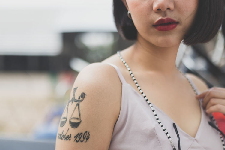Midsection of woman with tattoo standing outdoors