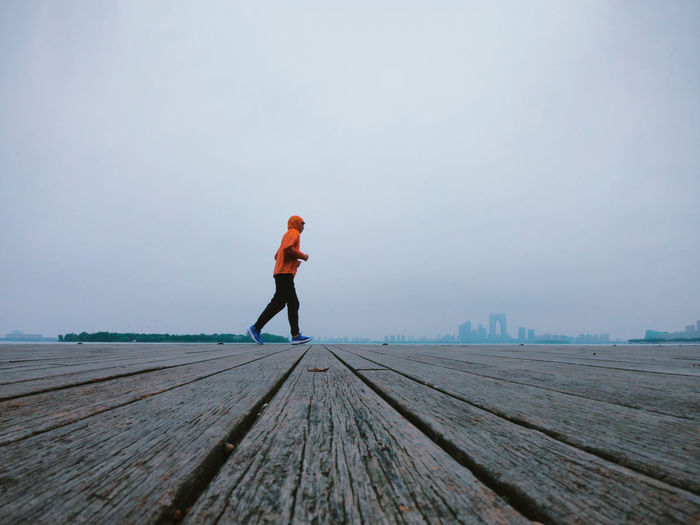 Side view of man jogging on boardwalk against sky