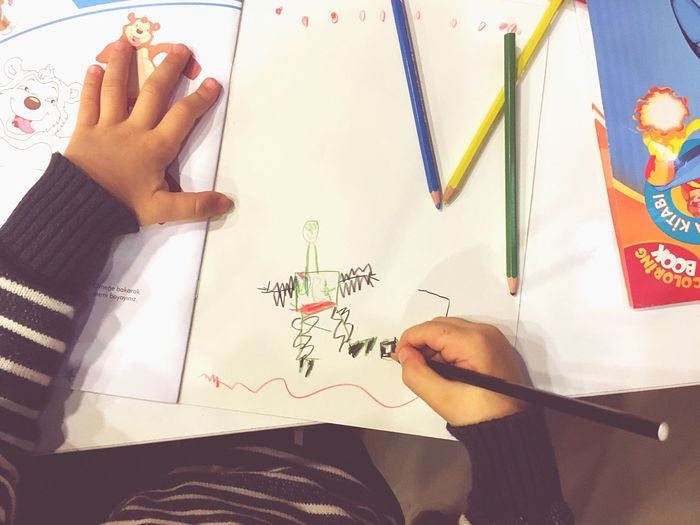 Midsection Of Kid Drawing On Paper