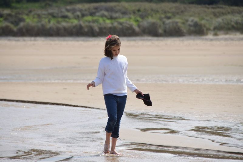 Full length of girl standing at shore during sunny day