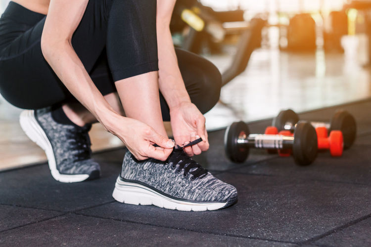 Woman tying her shoelaces with fitness equipment in the gym Adult Body Part Exercising Focus On Foreground Hand Healthy Lifestyle Human Body Part Human Hand Human Leg Human Limb Indoors  Leisure Activity Lifestyles Low Section People Real People Shoe Sport Sports Training Women