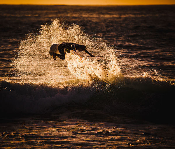 Side view of man surfboarding on sea during sunset