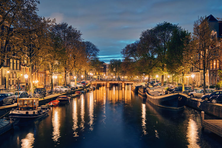 Sailboats moored on canal in city at night