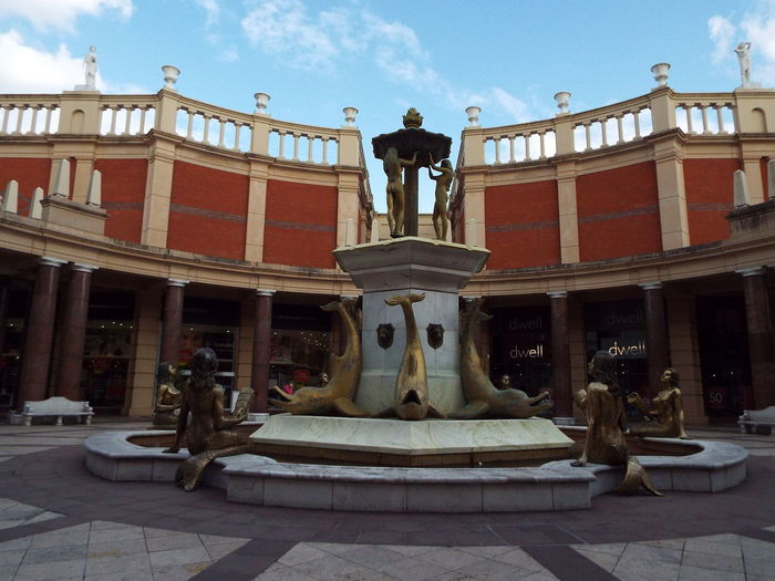 Barton Square Shopping Centre Retail  Water Fountain Fountain Mermaids Dolphins Statues Golden Statue Columns Blue Sky And Clouds Blue Sky And White Clouds Blue Sky White Clouds Blue Sky