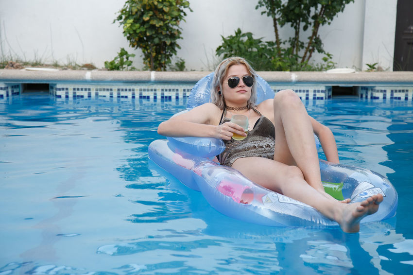 Young attractive woman lying on airbed and relaxing with beer in pool. Beautiful Beer Happy Holiday Lifestyle Relaxing Swimming Woman Young Airbed Bikini Comfort Drinking Enjoy Female Floating On Water Girl Inflatable  One Person Pool Rest Smiling Summer Vacation Water