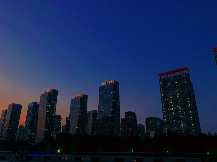 Illuminated Buildings Against Blue Sky At Dusk