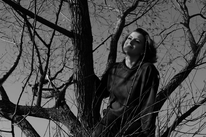 Thoughtful woman looking away while sitting on tree