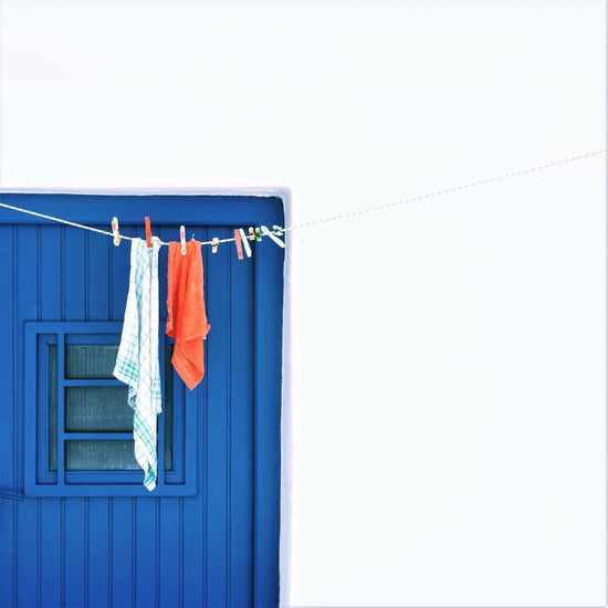 Clothes drying on clothesline against blue door