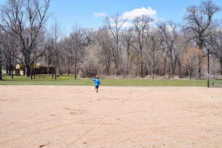 Full length of boy running on dirt road against bare trees
