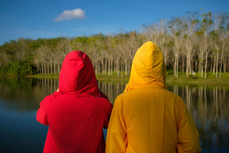 Rear View Of Female Friends Standing By Lake Against Trees