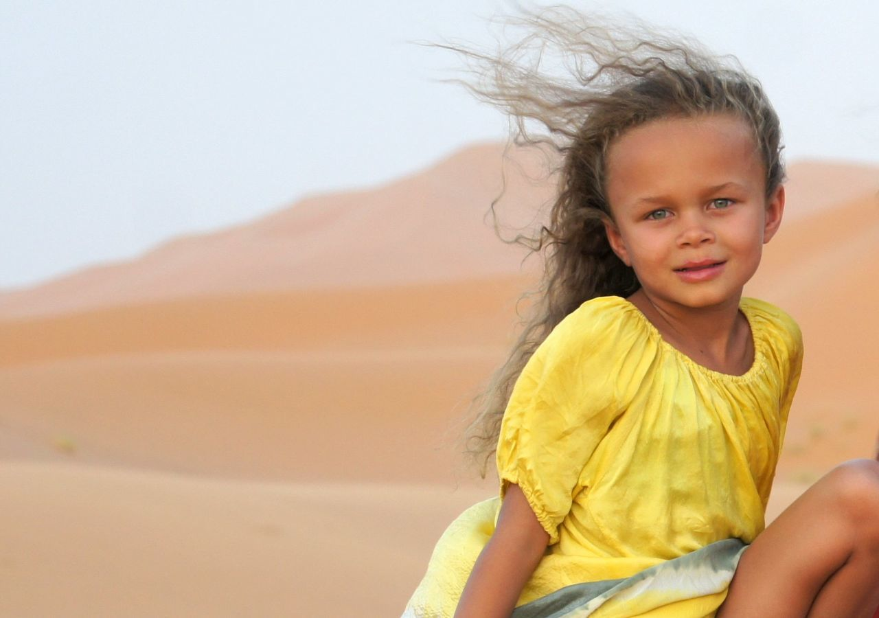 Portrait Of Smiling Girl On Sand At Beach