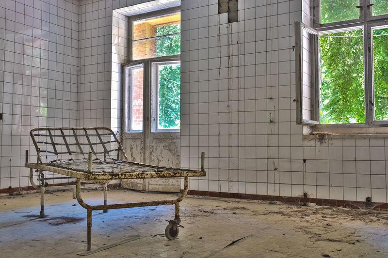 Rusty metal bed on floor in abandoned hospital