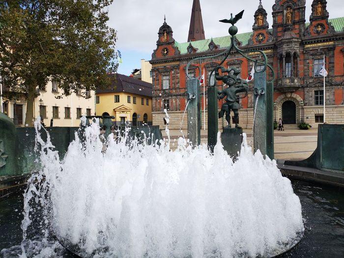 Fountain in city against sky