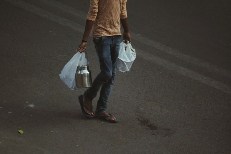 Low Section Of Man Carrying Plastic Bags While Walking On Road