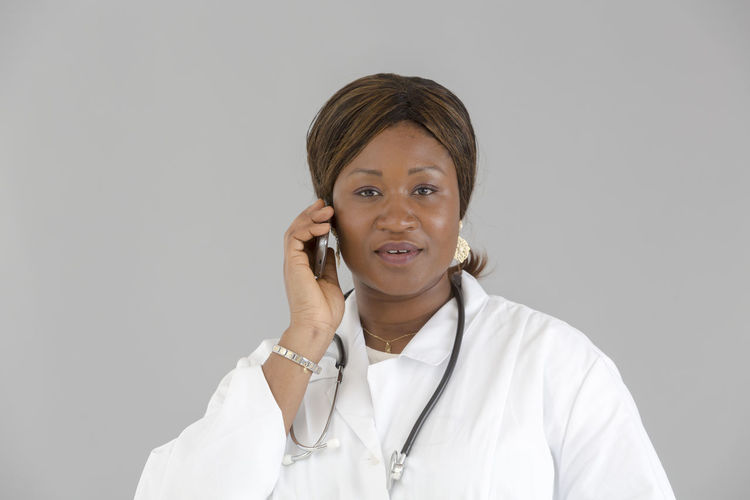 African Girl  Talking On The Phone Speaking On The Phone Front View Portrait Looking To The Camera Looking At Camera Smiling African Beautiful Woman Reassuring Reassurance Good News Occupation White Background Clinic Pediatrician Pediatrics Hospital Doctor  Nurse Medical Stethoscope