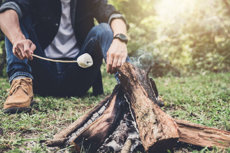 Low section of man preparing marshmallow while sitting on grassy field in forest