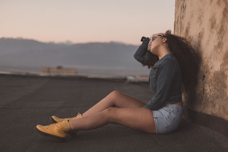 Fashionable young woman sitting by wall during sunset