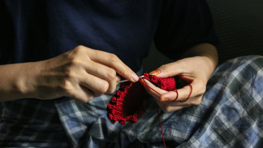 Midsection Of Person Knitting Red Wool