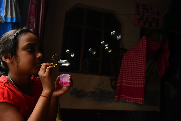 Girl blowing bubbles at home
