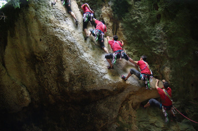 Low angle view of men climbing on rock formation
