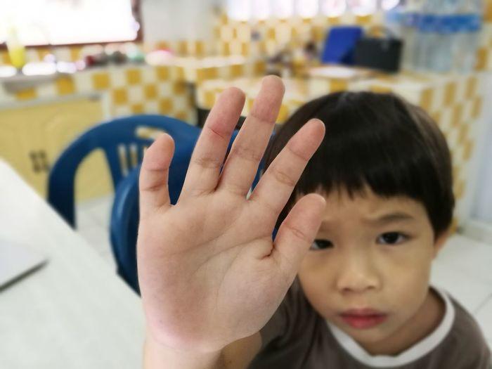 Portrait of boy showing hand