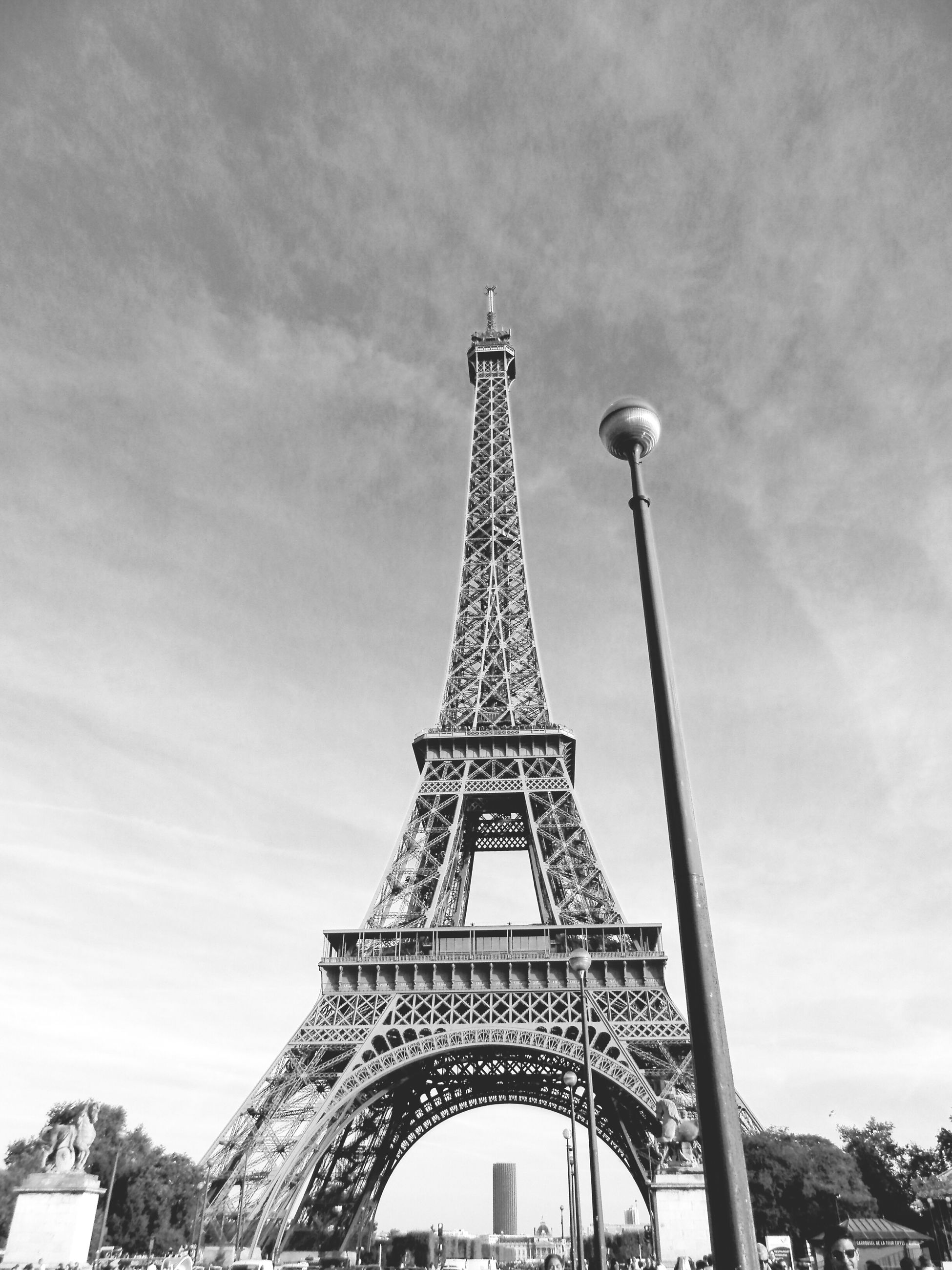 architecture, built structure, eiffel tower, famous place, international landmark, travel destinations, low angle view, culture, tourism, metal, tower, sky, capital cities, travel, history, tall - high, architectural feature, metallic, engineering, day