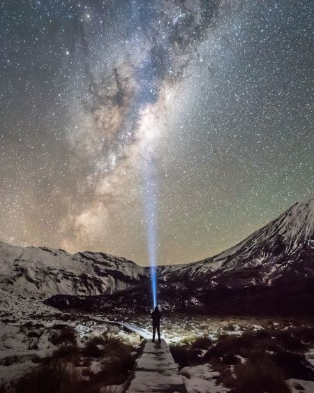 Person with illuminated flashlight against star field at night