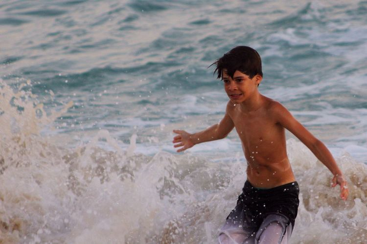 Teenage Boy Wading In Surf