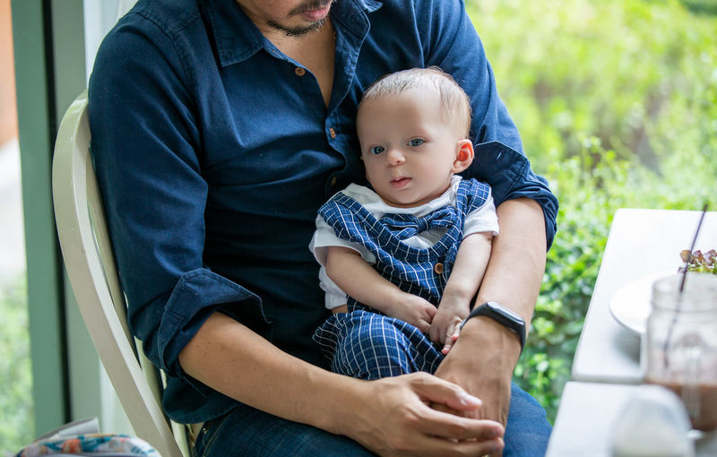 Midsection of father carrying cute son while sitting in cafe