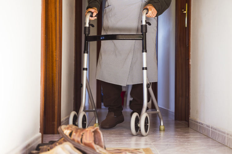 Low section of man with walker standing on tiled floor