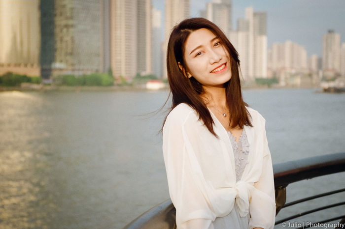 Architecture Beautiful Woman Building Exterior Built Structure City Day Lifestyles Long Hair One Person Outdoors People Real People Smiling Water Young Adult Young Women